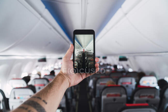 Airplane, man using smartphone, taking a picture interior — Stock Photo