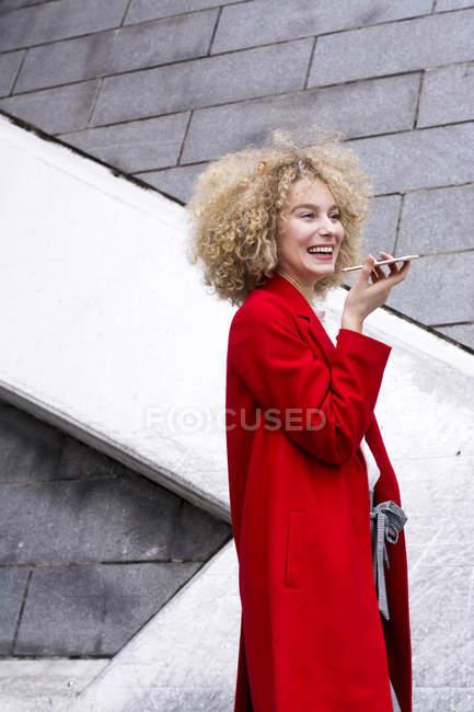 Портрет сміху білявої жінки з колечко носити червоне пальто і розмовляти по мобільному телефону — стокове фото