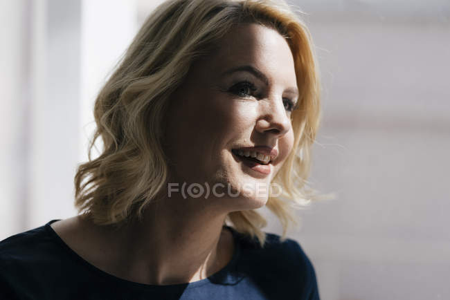 Portrait of smiling blond woman in sunlight at window — Stock Photo