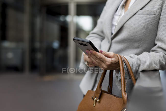 Close-up of businesswoman with cell phone and handbag — Stock Photo
