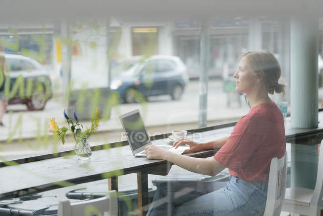 Young woman with cup of coffee and laptop sitting at the window in a cafe — Stock Photo