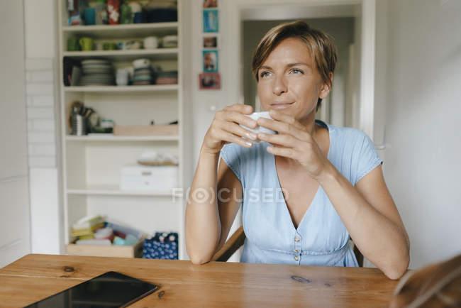 Жінка, сидячи за столом вдома з чашкою кави — стокове фото