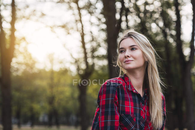 Portrait of young woman wearing plaid shirt in nature — Stock Photo