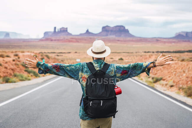 USA, Utah, Man with backpack standing on road to Monument Valley — Stock Photo