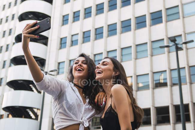 Lachende Freunde machen Selfie mit Handy — Stockfoto