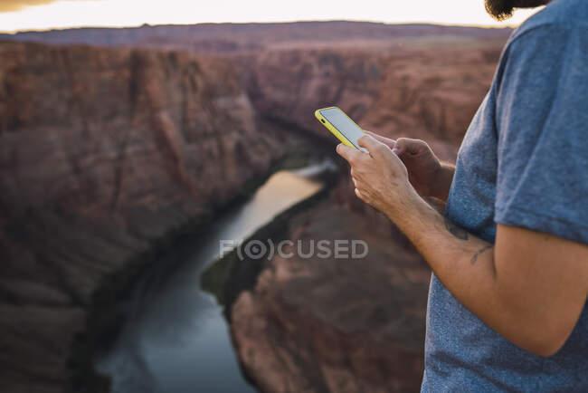 EUA, Arizona, Colorado River, Horseshoe Bend, jovem no miradouro usando smartphone — Fotografia de Stock