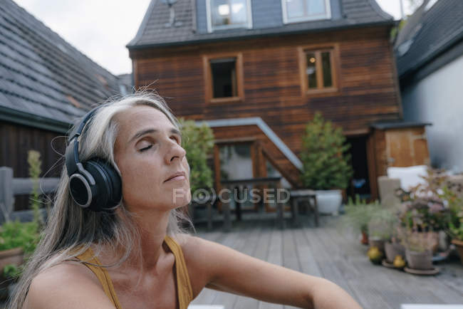 Portrait of mature woman listening music with headphones on terrace — Stock Photo