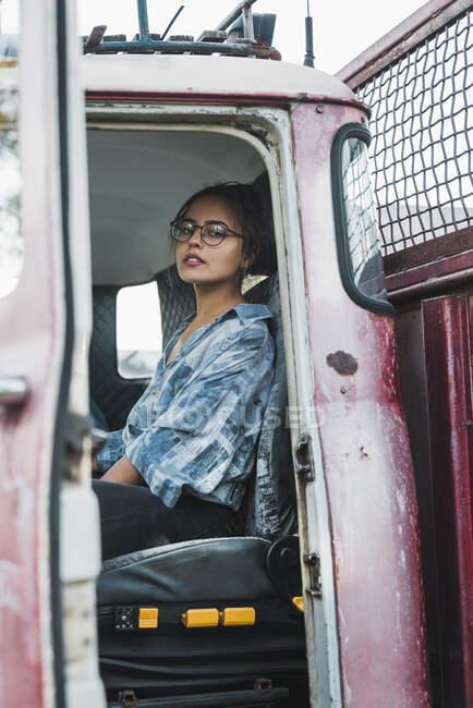 Молода жінка сидить у хатині розбитого старовинного вантажного автомобіля. — стокове фото