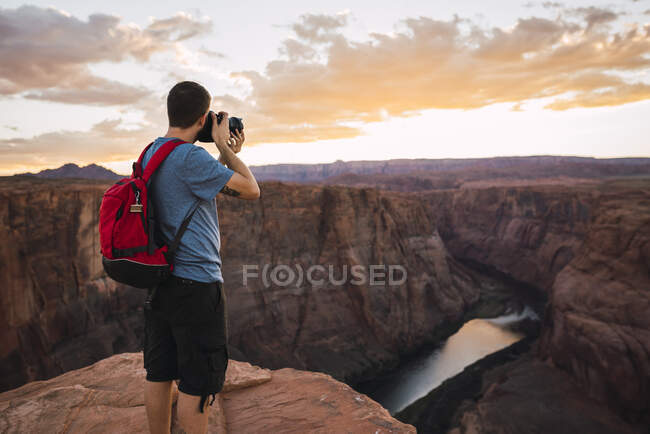 USA, Arizona, Colorado River, Horseshoe Bend, young man on viewpoint, photographing — Stock Photo