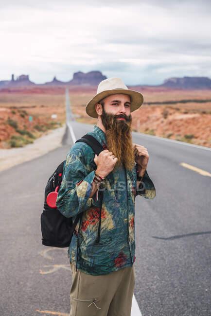 США, Юта, людина з рюкзаком стоїть на дорозі до Долини пам