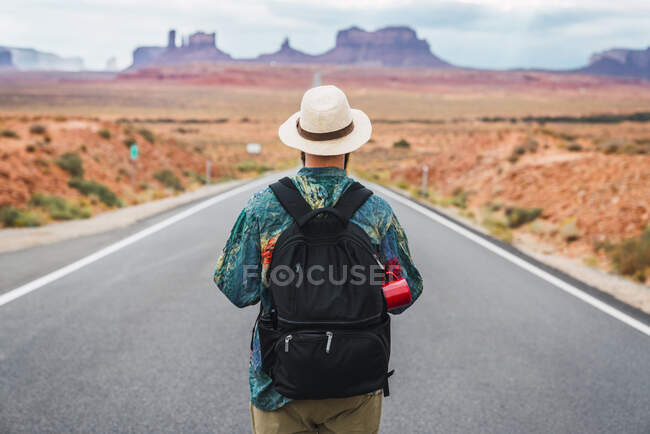 USA, Utah, Man with backpack standing on road to Monument Valley. - foto de stock