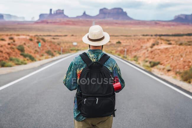 USA, Utah, Uomo con zaino in piedi sulla strada per Monument Valley — Foto stock