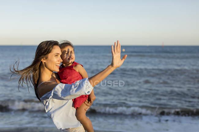 Mutter und Tochter stehen bei Sonnenuntergang am Strand — Stockfoto
