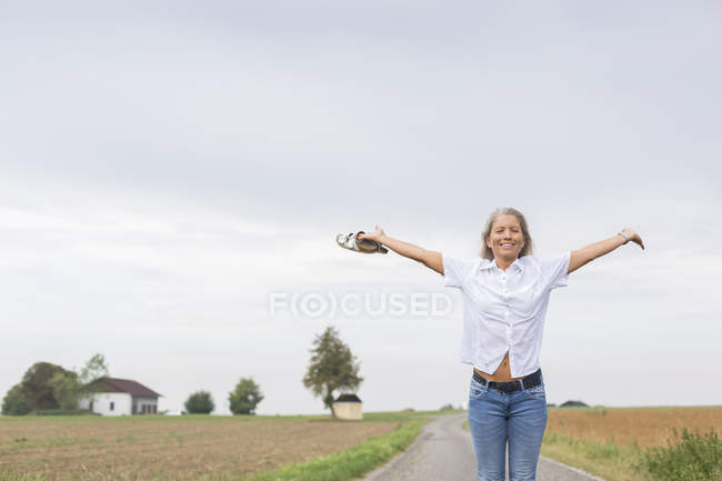 Reife Frau steht im Sommer mit ausgestreckten Armen auf abgelegenem Feldweg — Stockfoto