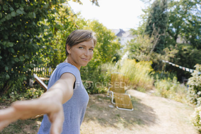 Portrait of smiling woman in garden reaching out hand — Stock Photo