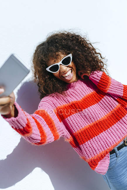 Ritratto di giovane donna che indossa occhiali da sole scattando selfie con cellulare — Foto stock