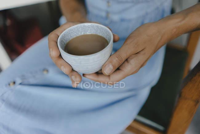 Primo piano della donna che tiene in mano una tazza di caffè con latte — Foto stock
