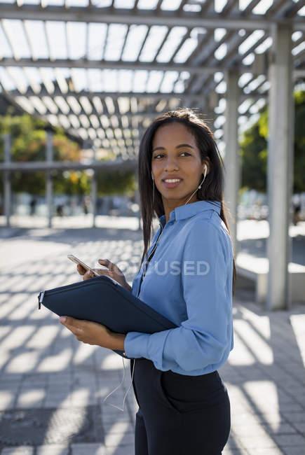 Femme d'affaires utilisant un smartphone, tenant sac d'ordinateur portable — Photo de stock