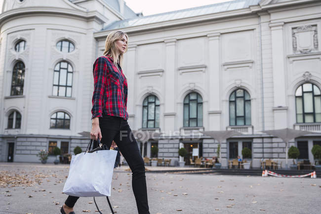 Fashionable young woman with shopping bag walking on street — Stock Photo