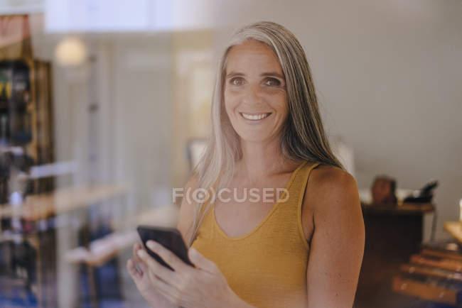 Retrato de una empresaria sonriente con teléfono celular en su tienda - foto de stock