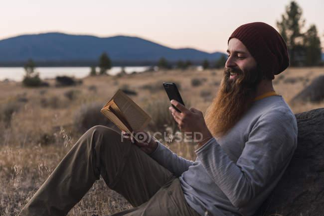 EE.UU., norte de California, joven barbudo con libro y teléfono celular durante un viaje de senderismo cerca del Parque Nacional Volcánico Lassen - foto de stock