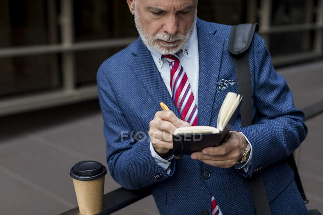 Senior businessman writing in diary outdoors — Stock Photo