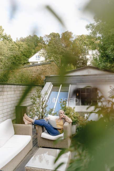 Donna con laptop rilassante sulla terrazza — Foto stock