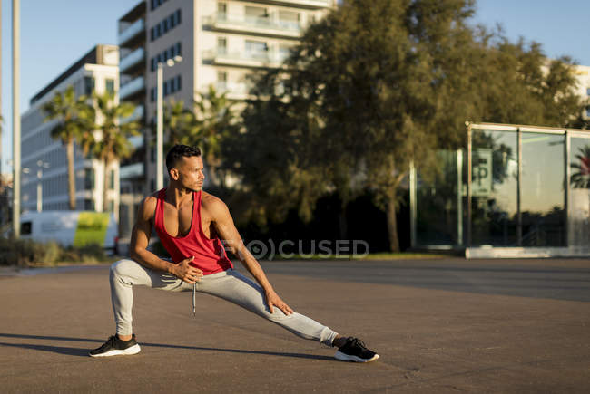 Fit man warming up before workout, doing lunges — Stock Photo