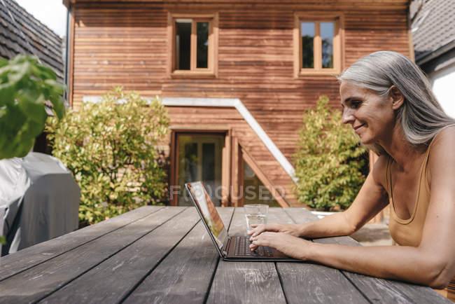Женщина сидит на террасе своего дома и использует ноутбук — стоковое фото
