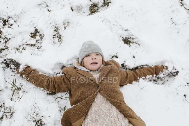 Portrait of boy lying on snow-covered meadow making a snow angel — Stock Photo