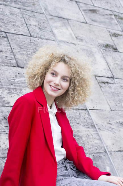 Портрет усміхнена білява жінка з колечко носити червоне пальто — стокове фото