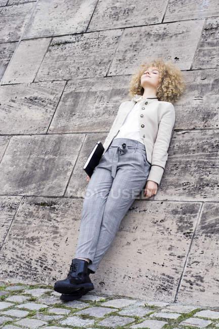 La mujer a la moda rubia con la carpeta apoyada en la pared y descansando - foto de stock