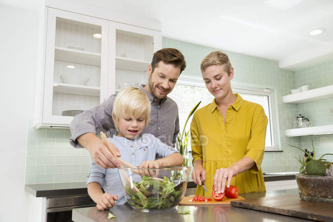 Smiling family preparing salad in kitchen together — Stock Photo