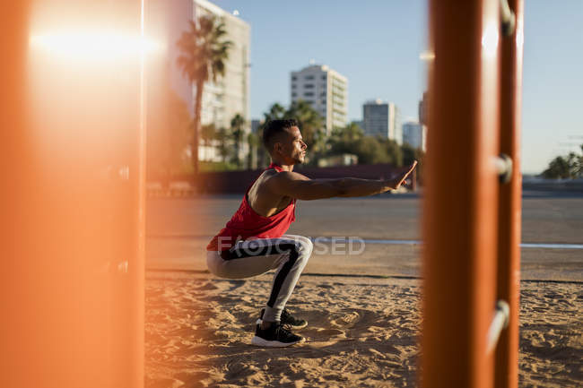 Fit man working out in climbing parcour, doing squats — Stock Photo
