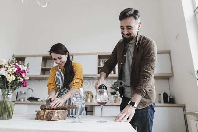 Happy couple preparing lunch together in the kitchen — Stock Photo