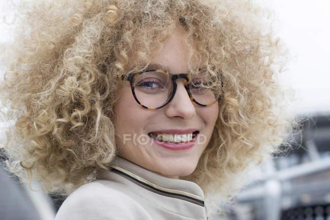 Ritratto di donna bionda sorridente con riccioli che indossano occhiali alla moda — Foto stock