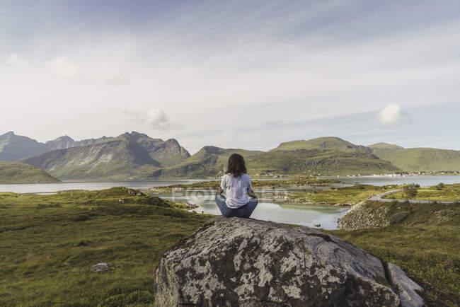 Молода жінка сидить на скелі, дивлячись на вид, медитуючи (Лапландія, Норвегія). — стокове фото