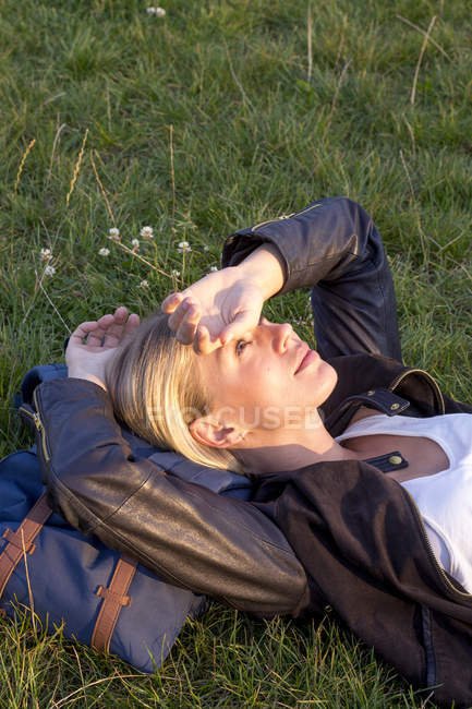 Woman lying on a meadow in a park and relaxing — Stock Photo