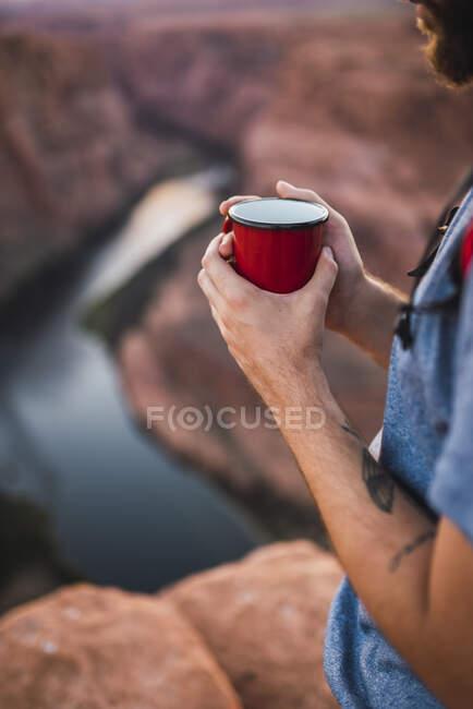Молодий чоловік тримає червону чашку. — стокове фото