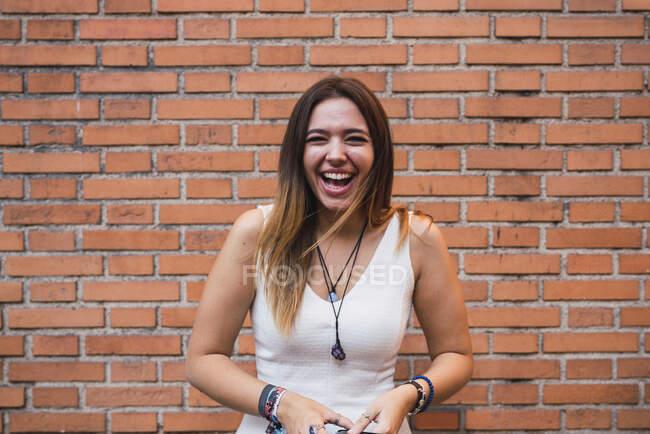 Portrait d'une jeune femme riante debout devant un mur de brique — Photo de stock