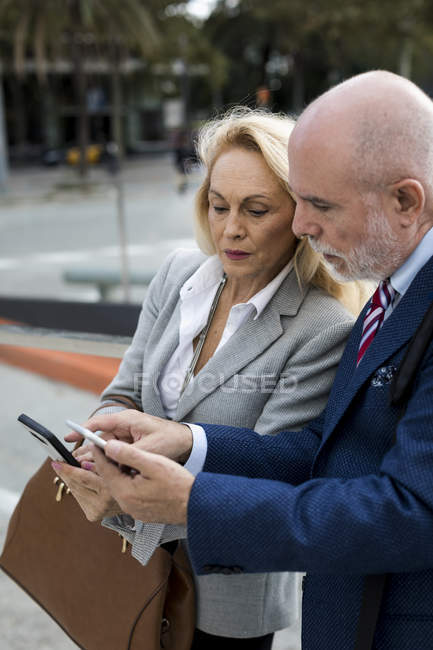 Senior businessman and businesswoman using cell phones in the city — Stock Photo