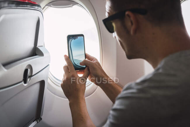 Man in airplane, using smartphone, taking a picture, airplane window — Stock Photo