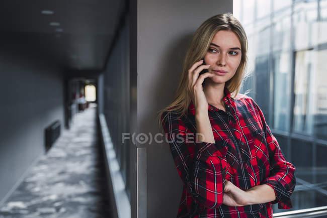 Retrato de jovem ao telefone em um prédio de escritórios moderno — Fotografia de Stock