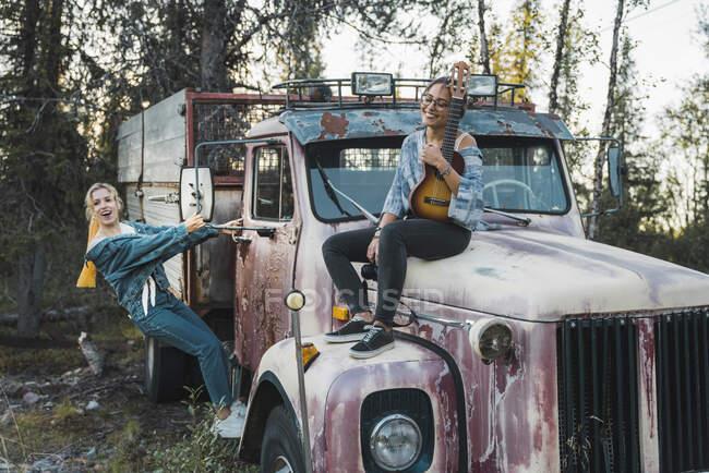 Двоє друзів сидять на розбитій вантажівці і грають на укулеле. — стокове фото