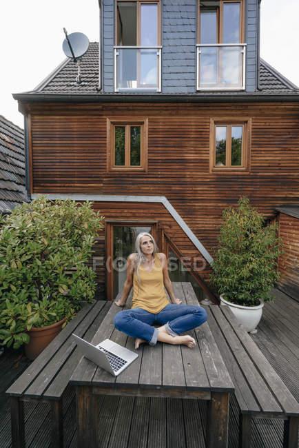 Donna rilassante sul tavolo del giardino al cortile della sua casa — Foto stock