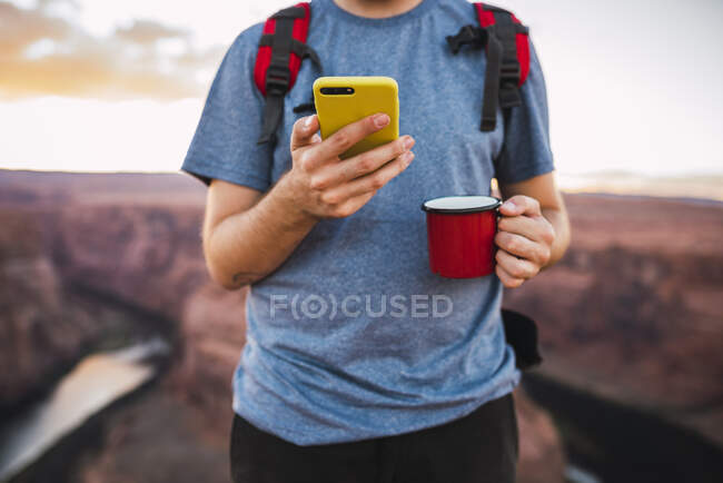 Young man holding red cup and using smartphone — Stock Photo