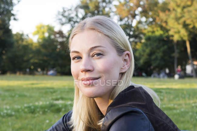 Retrato de conteúdo mulher loira relaxante em um parque — Fotografia de Stock