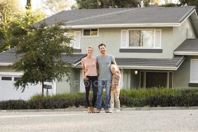 Retrato de pais sorridentes com o menino de pé na frente de sua casa — Fotografia de Stock