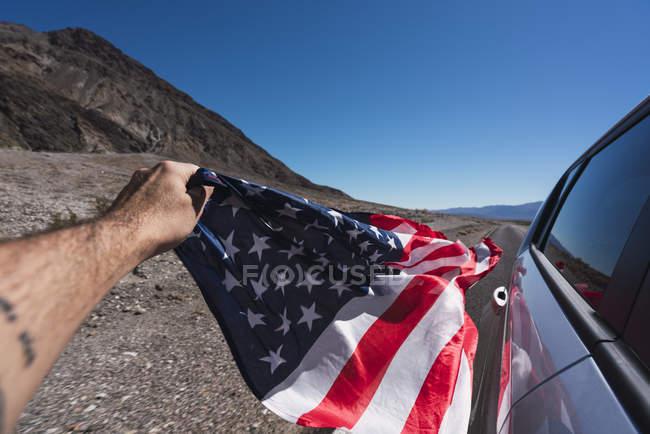 Usa, California, Death Valley, la mano dell'uomo che tiene bandiera americana oltre all'auto — Foto stock