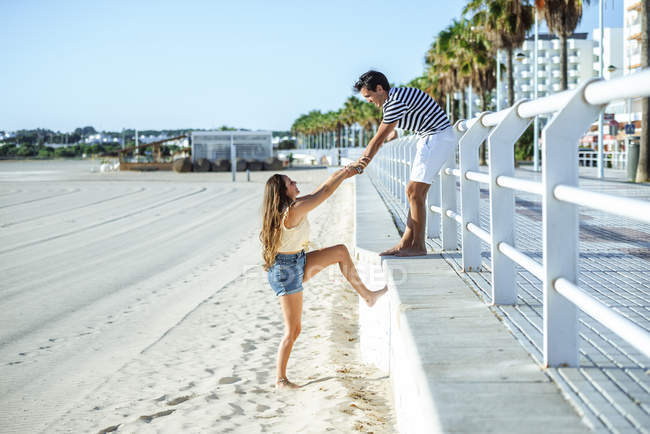 Man helping woman to climb up from the beach to the promenade — Stock Photo